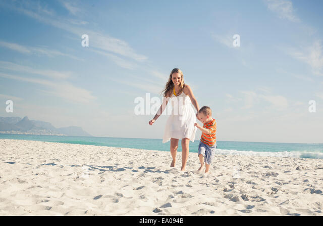 Boy running and pulling mother on beach, Cape Town, Western Cape, South Africa - Stock Image