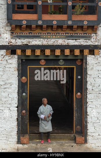 An older man in the traditional gho exits the bridge gatehouse of the Punakha Dzong.  Bhutan. - Stock Image
