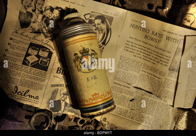 An old thermos flask lying on an old piece of newsprint in a box of nuts and bolts - Stock-Bilder