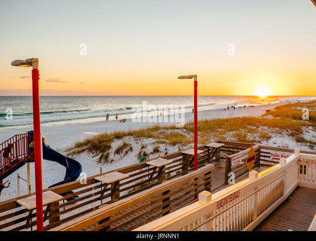 Sunset on a popular white sand beach in the Florida panhandle near Destin where families go for a vacation or on - Stock Image