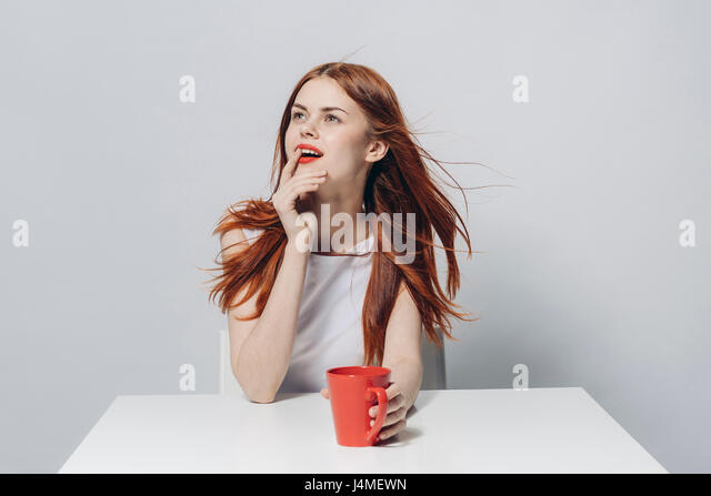 Pensive Caucasian woman sitting at windy table holding red cup - Stock-Bilder