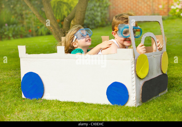 Boy and Girl Wearing Goggles Driving Cardboard Car - Stock Image