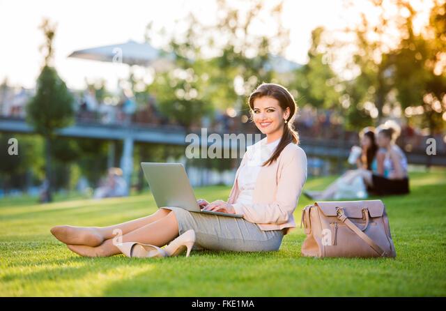 Businesswoman sitting in park working on laptop, sunny summer da - Stock Image