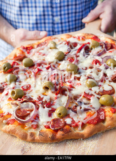 a grilled pizza with olives and onions on cutting board - Stock Image