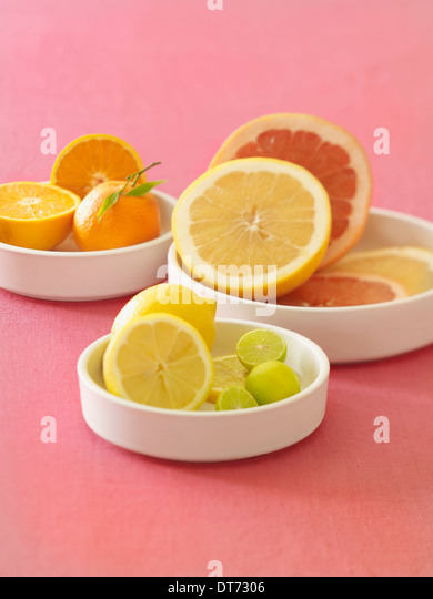 A white platter with oranges, blood oranges, grapefruit, lemon and limes on a pink fabric background. - Stock-Bilder