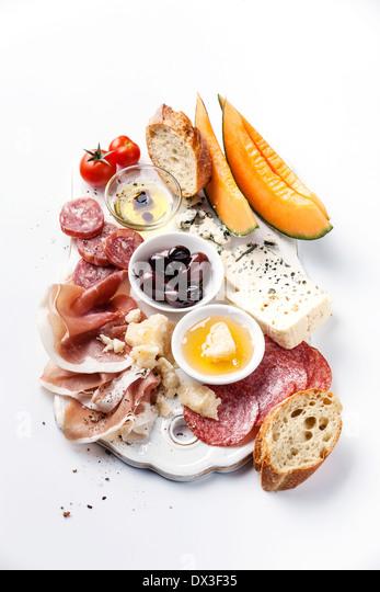 Antipasti ham, cheese, melon, olives, olive oil, bread - Stock Image