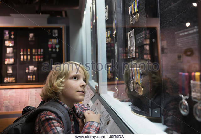 Curious boy student looking up at exhibit on field trip in war museum - Stock-Bilder