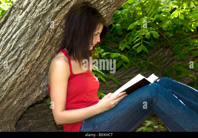 A beautiful young woman leans against a tree and reads the bible, learning verses. Oklahoma, USA. - Stock Image