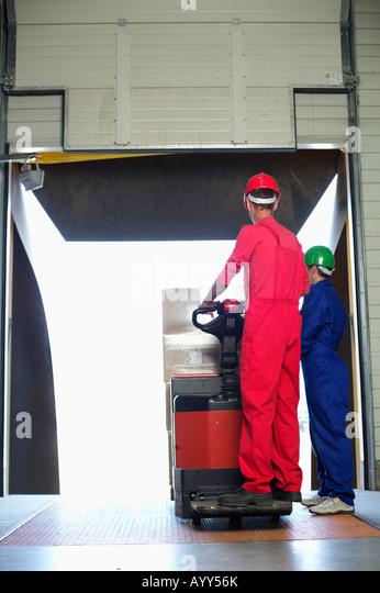 Man handling an electric lifting cart - Stock Image