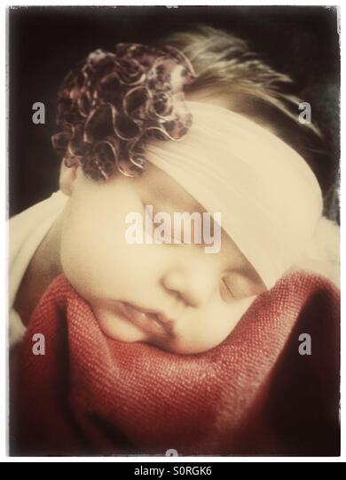 Sleeping baby wearing a headband with a flower - Stock Image