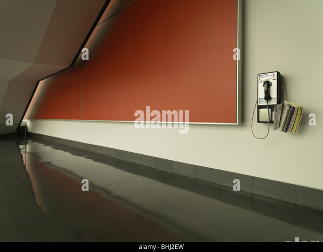 Coin operated phone on wall - Stock Image