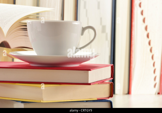 Composition with stack of books and cup of coffee - Stock Image