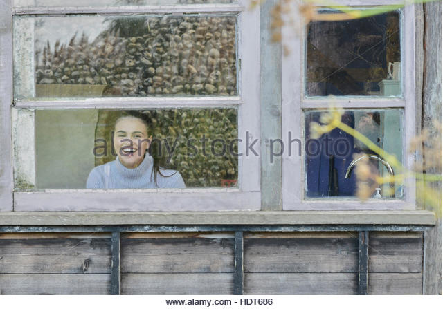 Young woman laughing at log cabin window. - Stock Image