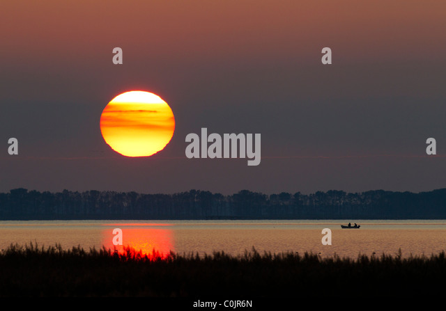 Fishermen in rowing-boat on lake at sunset, Western Pomerania, Germany - Stock Image