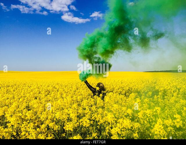 Green Smoke Emitting From Woman Hand Holding Distress Flare On Raps Field - Stock Image