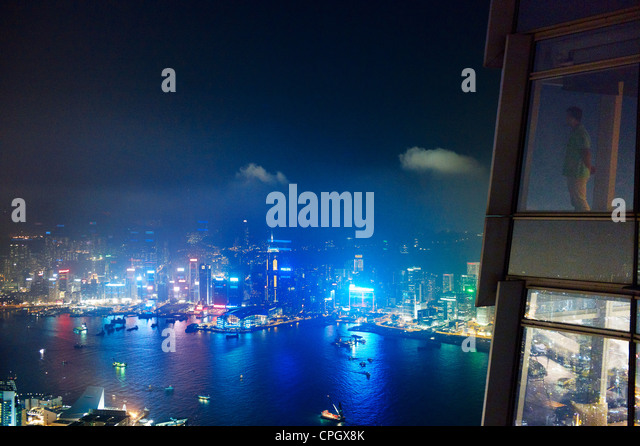 A man looks out at Central Hong Kong at night from the International Commerce Centre - Stock Image