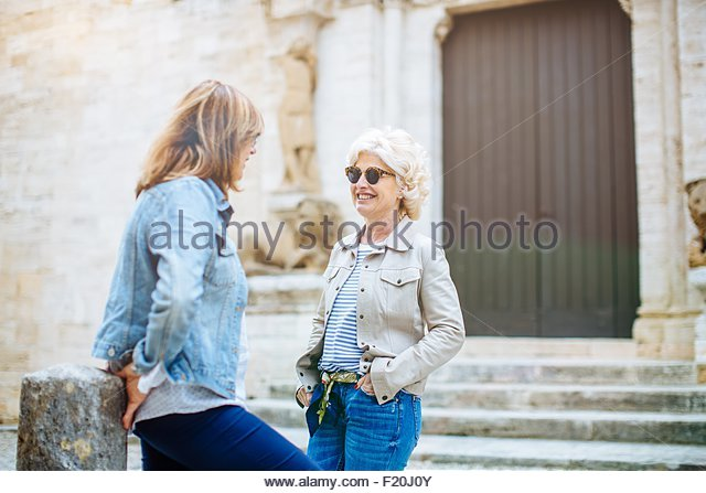 Two mature female friends talking in front of historic building, Tuscany, Italy - Stock Image