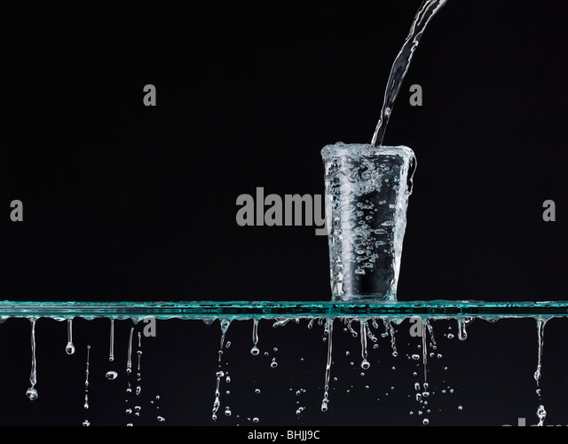Pouring water into a glass, Overflowing - Stock Image