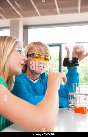 Schoolboy and schoolgirl experimenting in chemical class - Stock Image