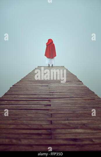 Lone woman dressed with red hooded robe in a misty pier - Stock-Bilder