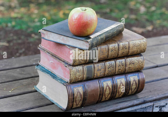 Apple sitting atop pile of old books - Stock Image