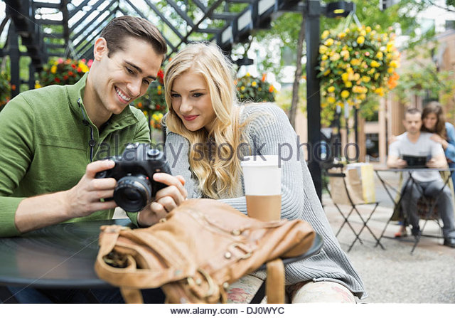 Couple looking at photographs on camera - Stock Image
