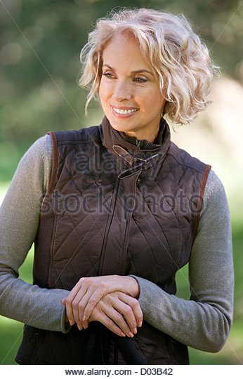 A portrait of a mature woman outdoors, smiling - Stock Image