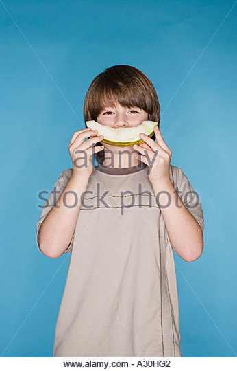 Boy with a melon smile - Stock Image