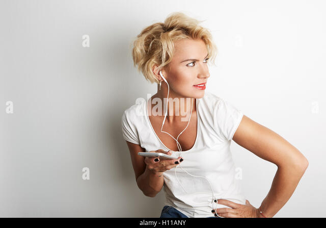 Stylish Blande Female Listening Music Earphones Smartphone While Standing Against White Background.Copy Space Your - Stock Image
