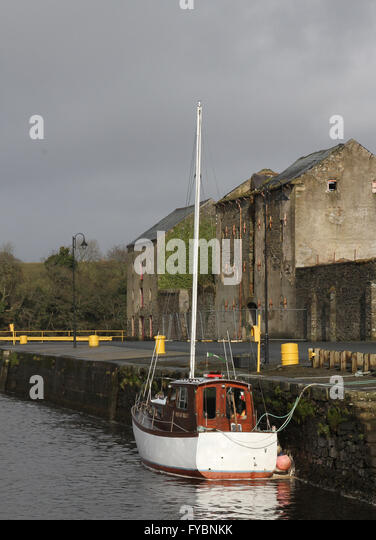 Old store building on the quayside at Ramelton County Donegal. The boat on the River Lennon is the 'Mist of - Stock Image