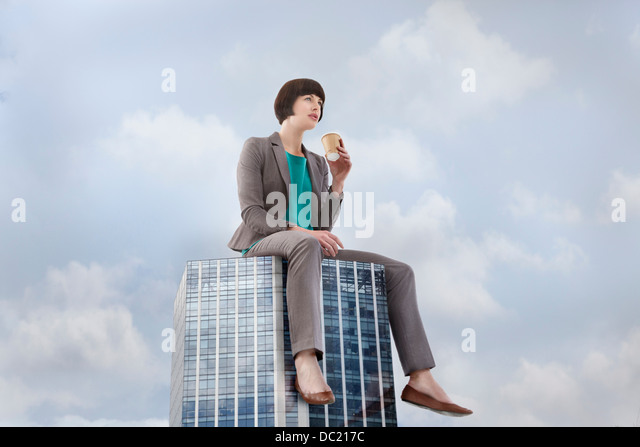 Oversized businesswoman sitting on skyscraper, low angle view - Stock Image