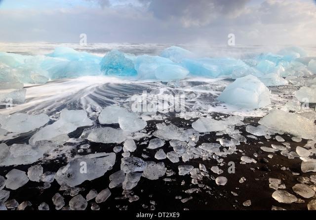 IceBergs and waves on Jokulsarlon Beach, Polar region, South Iceland - Stock Image