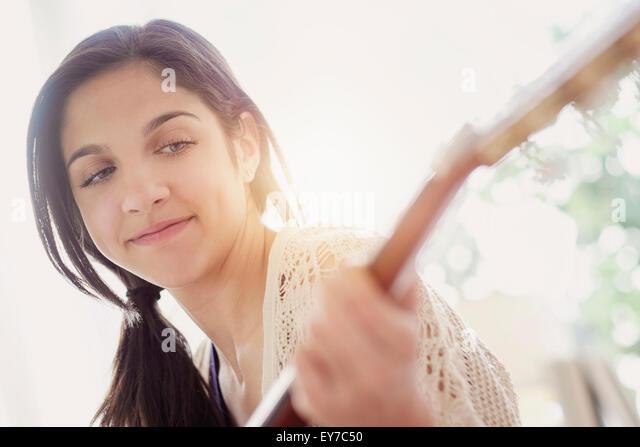 Teenage girl (14-15) playing guitar - Stock Image
