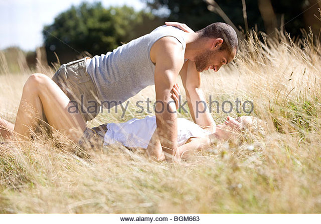 A young romantic couple lying on the grass - Stock-Bilder
