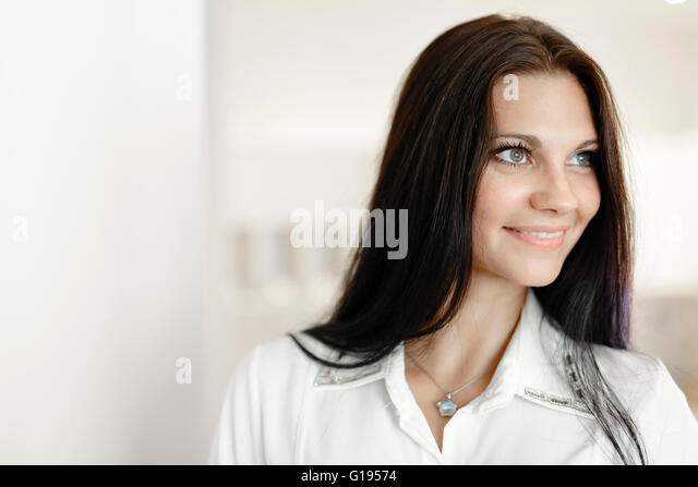 Beautiful woman in shirt in her home being positive and happy - Stock Image