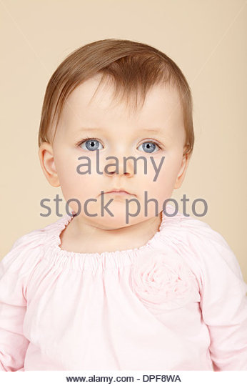 Close up studio portrait of baby girl with blue eyes - Stock Image