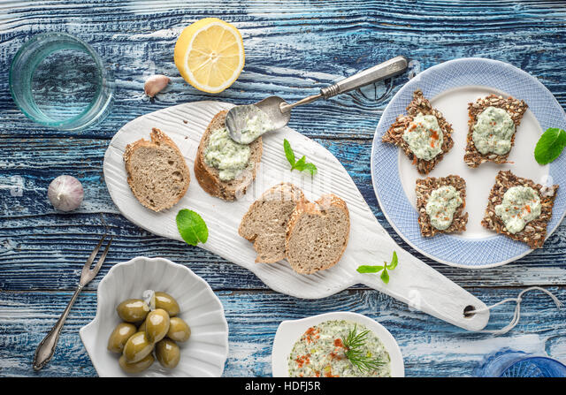 Bread with tzatziki on the blue wooden table with accessorize top view - Stock Image