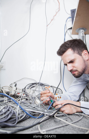 Frustrated man lying down trying to figure out and sort  computer cables - Stock Image