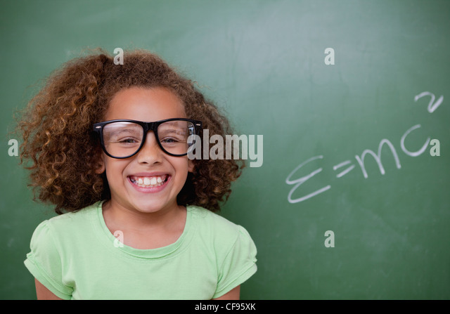 Schoolgirl posing with the the mass-energy equivalence formula - Stock Image