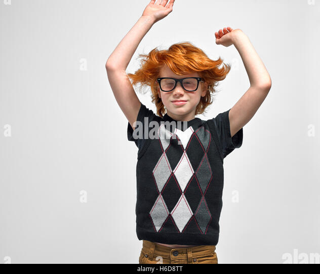 youth boy wearing glasses arms up and hair flying around waist up - Stock Image
