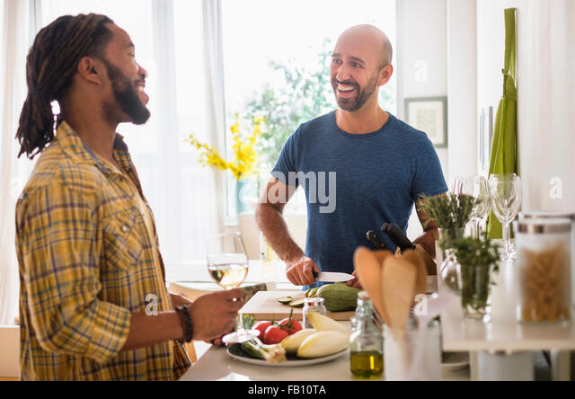Smiley homosexual couple drinking wine in kitchen - Stock Image