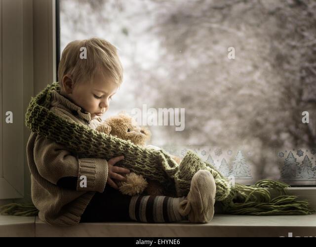 Boy sitting on a window sill with a teddy bear - Stock Image