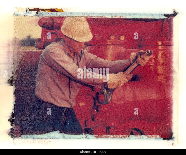 Oil industry worker tightening bolts on pump at a drilling rig image is artistic polaroid transfer technique - Stock Image