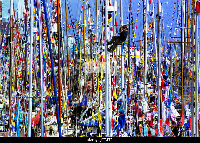 A boy sailor in a bosun's chair climbs a mast at the Festival of the Sea when 1000 sailing ships gathered in - Stock Image