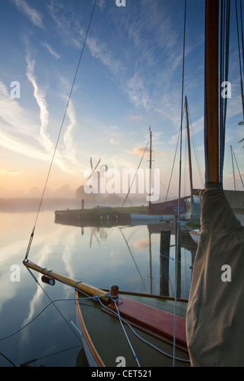 View over the bow of a sailing boat on the River Thurne through dawn mist towards Thurne drainage mill on the Norfolk - Stock-Bilder