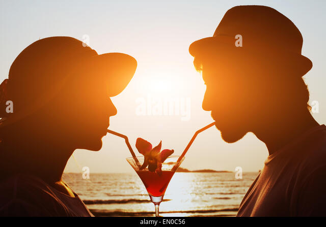 party time, couple drinking cocktail together on the beach during their honeymoon - Stock Image