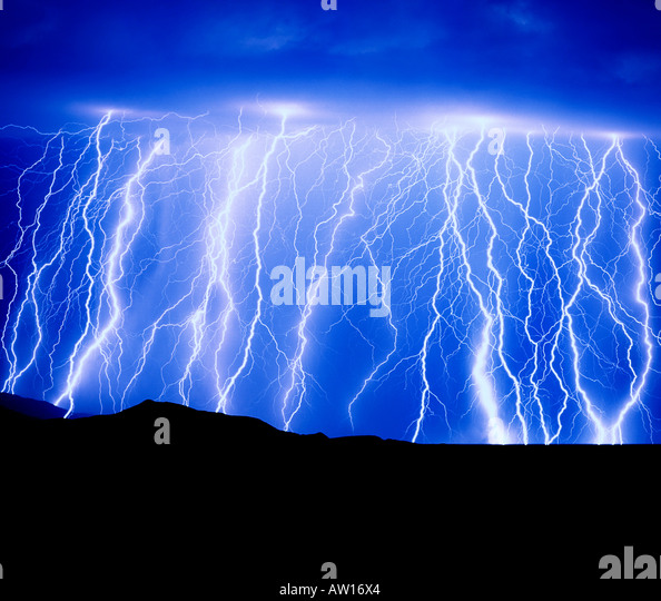 Blue Graphic Sky Lightning and monsoon rainstorm shower produces multiple Skystrikes  from  dark clouds in the Rincon - Stock Image