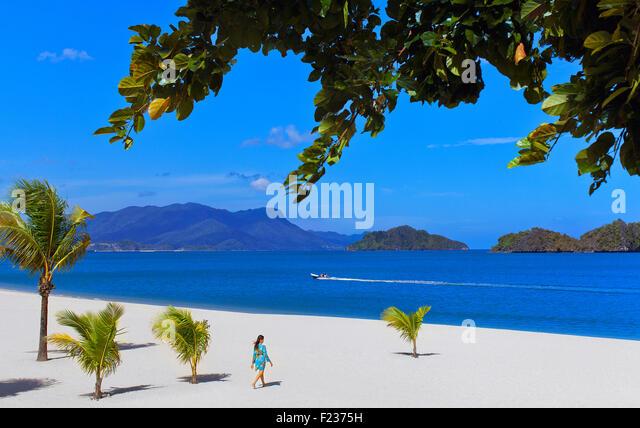 A guest walks toward the ocean at Four Seasons Langkawi. Langkawi, Malaysia. - Stock Image