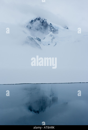 Peak of an antarctic mountain showing through the mist and reflected in the deep blue waters beneath - Stock Image