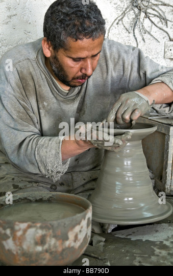 Man throwing an earthenware plate at factory near Fez, Morocco - Stock Image